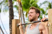 Crossfit man working out pull-ups on chin-up bar. Portrait of bearded fit young man cross training arms on horizontal bars outside on outdoor gym in summer.