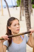 Exercise woman training arms on pull-up bar doing chin-ups. Asian mixed race chinese caucasian female athlete working out on horizontal bars outside on beach.