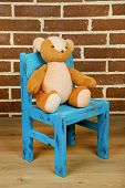 Bear toy on chair on brick wall background