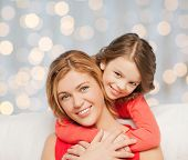 people, happiness, love, family and motherhood concept - happy mother and daughter hugging over holidays lights background