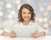people, technology and children concept - happy smiling girl with tablet pc computer over holidays lights background