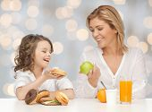 people, healthy lifestyle, family and food concept - happy mother and daughter eating healthy breakfast over holidays lights background