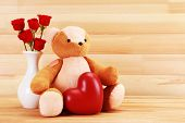 Teddy bear with heart and roses on wooden background, love concept