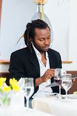 Business man, african american, with tablet in restaurant having lunch in restaurant