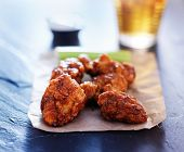 beer and spicy boneless chicken wings on slate
