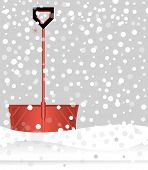 Red snow shovel in falling snow