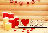 Romantic candles on wooden background, love concept