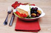 foto of brie cheese  - aged brie cheese on salad in white dish over red cloth on with olives and tomato over wooden table - JPG