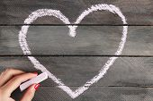 Hand draws heart of chalk on wooden board
