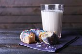Crumbled donut on napkin with glass of milk on rustic wooden planks background