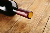 Lying red wine bottle on wooden table