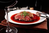 Glass of wine with grilled steak in wine sauce on dark background