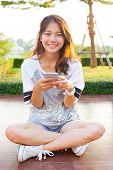 Young Teen Woman And Smartphone In Hand Smiling With Happy Emotion
