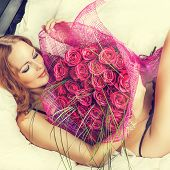Woman In Bed With A Big Bouquet Of Red Roses