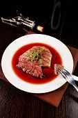 Grilled steak in wine sauce with bottle of wine on dark background