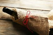 Wine bottle wrapped in burlap cloth on wooden planks background