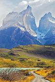 Summer day in the national park Torres del Paine, Patagonia, Chile. A dirt road leads to the cliffs of Los Kuernos