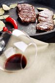 Glass of wine and steak in frying pan on table close up