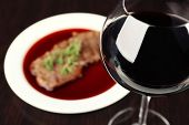 Glass of wine with steak on wooden background