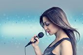 Winter song. Portrait of a beautiful woman with a microphone