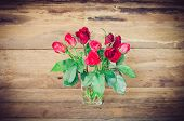 Red Roses In Glass On Wooden Bacgrould