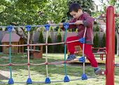 stock photo of playground school  - Child palying at children playground climbing on rope ladder obstacle course equipment - JPG