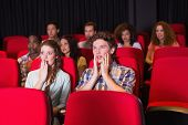 Surprised young friends watching a film at the cinema