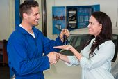 Mechanic giving keys to satisfied customer at the repair garage