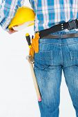 Rear view of handyman wearing tool belt while holding hard hat on white background