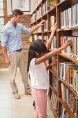 Cute pupils and teacher looking for books in library at the elementary school