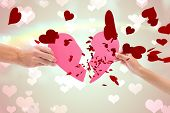 Hands holding two halves of broken heart against heart pattern on abstract design
