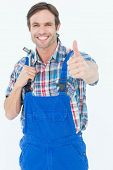 Portrait of confident plumber holding tool while gesturing thumbs up over white background