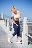 Fit blonde listening to music on the pier on a sunny day