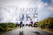 Excited couple jumping on the road against enjoy life more
