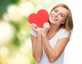 happiness, health, people, holidays and love concept - smiling young woman in white t-shirt holding red heart over green background