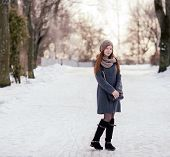 foto of stroll  - Winter full length portrait of a cute redhead lady in grey coat and scarf strolling in the park - JPG