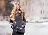 Winter portrait of a cute redhead lady posing on the street