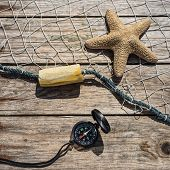 Nautical Border With Fishing Net, Sea Shells And Starfish On A Background Wooden Boards