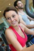 Woman in fitness club using cardio equipment