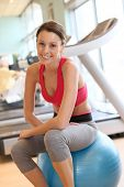 Athletic girl sitting on fitness ball