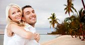 summer holiday, vacation, dating, travel and tourism concept - happy couple having fun and hugging over beach background