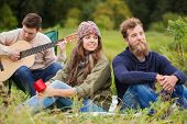 adventure, travel, tourism and people concept - group of smiling friends with guitar in camping