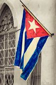 Cuban flag on a grunge decaying neighborhood in Havana