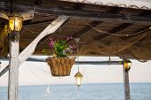 stock photo of hook  - Beautiful hanging basket with artificial flowers hooked on a wooden shelter on the sea shore surrounded by glowing vintage lamps - JPG