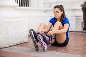 picture of skate  - Beautiful young woman putting her inline skates on before going skating  - JPG