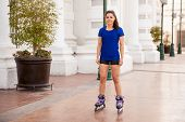 stock photo of inline skating  - Full length portrait of a gorgeous young woman skating in the city - JPG