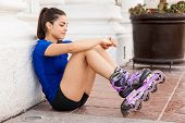 stock photo of inline skating  - Cute female skater sitting in the ground and relaxing after skating for a while in the city - JPG