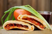 picture of scallion  - Two pieces of pizza calzone with glass of red wine fresh scallion and tomato on wooden board closeup macro horizontal - JPG