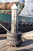 image of dock  - A dock pylon with used tires around it are used as means to tie up barges as they rest in their slips  - JPG