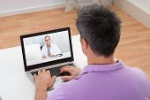 pic of video chat  - Man Having Video Chat With Doctor On Laptop At Home - JPG
